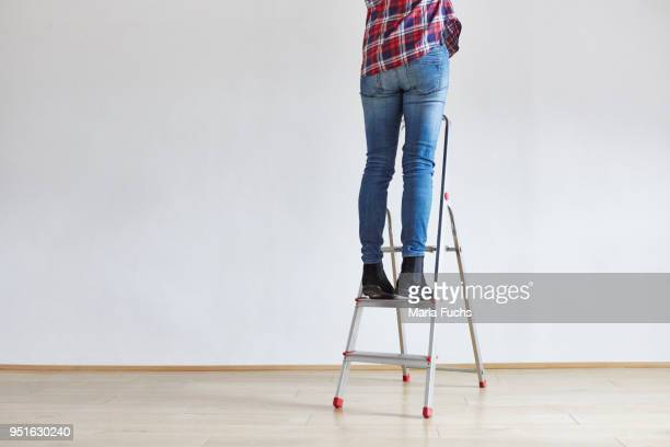 person standing on ladder - step ladder stock photos and pictures