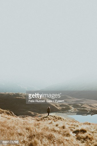 Person Standing On Landscape Against Sky