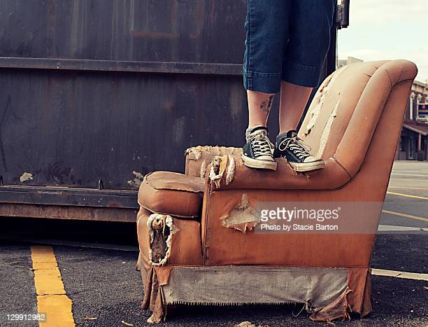 Person standing on old pink chair by dumpster