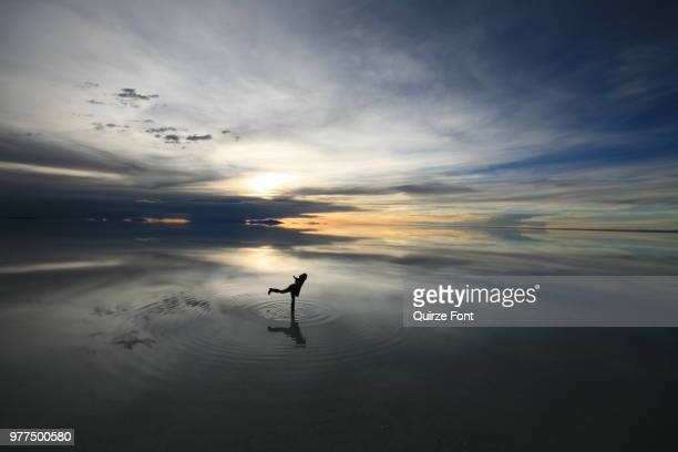 person standing on one leg in salar de uyuni at sunset, daniel campos province, potosi department, bolivia - potosí potosí department stock pictures, royalty-free photos & images
