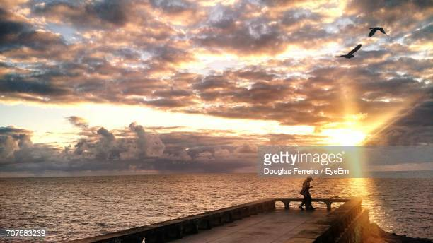 person standing on pier by sea against cloudy sky during sunset - olinda imagens e fotografias de stock