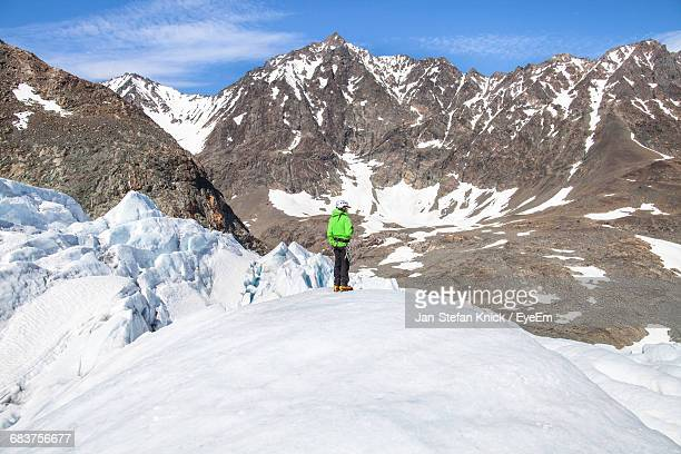 person standing on snow covered landscape against mountain range - crevasse stock photos and pictures