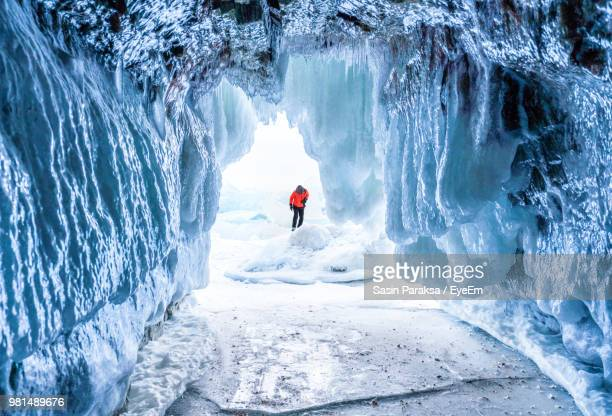 Person Standing On Snow Seen Through Cave Entrance