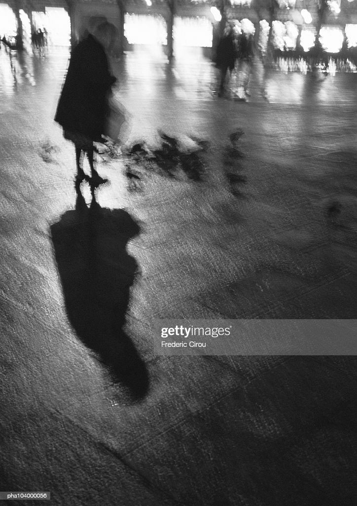 Person standing on wet pavement, blurred, b&w : Stockfoto