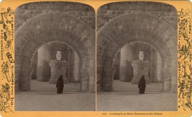 A person standing under the arched entrance of the Saint Paul Winter Carnival's ice palace Saint Paul Minnesota 1887 Inside the palace there is an...