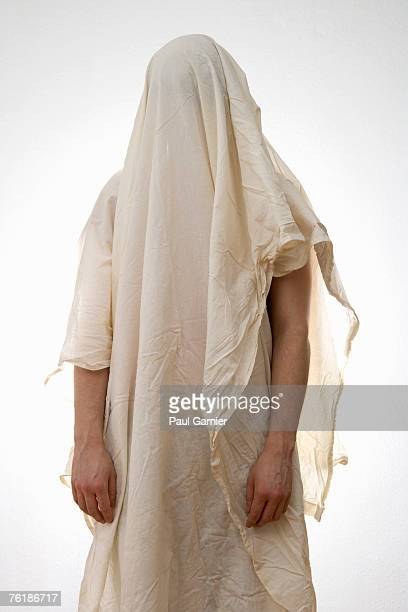 A person standing underneath a white sheet