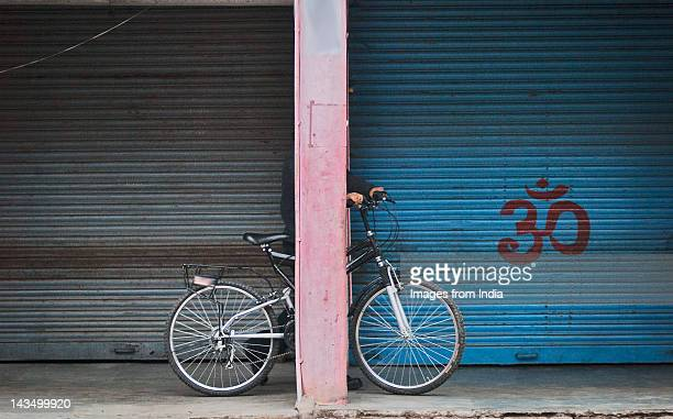 Person standing with cycle behind pillar