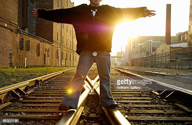 Person standing with open arms of railroad tracks