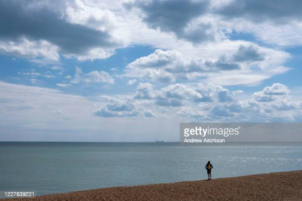 Person stands alone on Folkestone seafront looking out across Hythe Bay toward Dungeness Power station on the 4th of June 2020, Folkestone, United...
