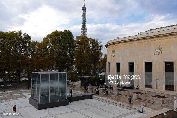 A person stands atop a staircase in a glass cube containing an olfactory cloud Le Nuage Parfumé or OSNI 1 launched by Cartier and displayed in front...