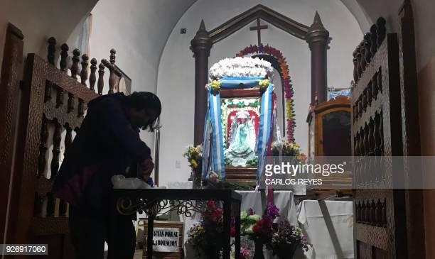 A person stands by the altar of the Virgin of Copacabana del Abra de Punta Corral at 'Nuesta Senora del Rosario' parish church in Tilcara Jujuy...