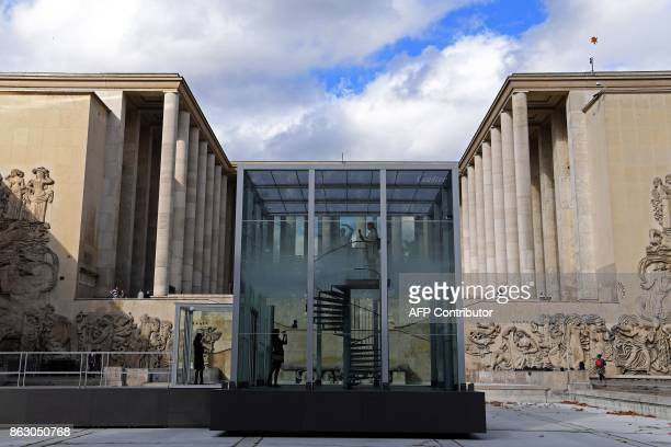 A person stands in a glass cube containing an olfactory cloud Le Nuage Parfumé or OSNI 1 launched by Cartier and displayed outside the Palais de...
