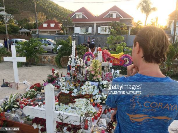 Person stands in front of the tomb of French rock singer Johnny Hallyday on June 15, 2018 in the Lorient cemetery on the French Caribbean island of...