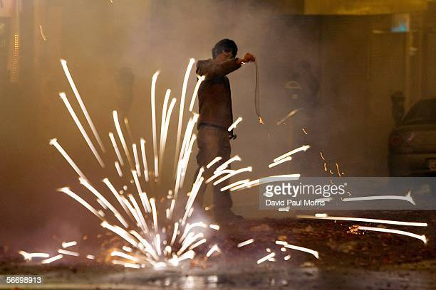 A person stands near fireworks as he celebrates Chinese New Year on January 29 2006 in Chinatown San Francisco California The Lunar New Year...