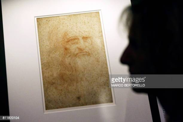 A person stands next to the selfportrait of Leonardo Da Vinci at the exhibition The World of Leonardo a collection of drawings of artists who appear...