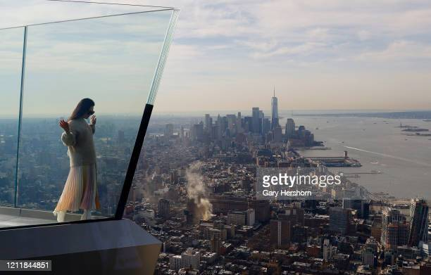 A person stands next to the skyline of lower Manhattan on the opening day the Edge NYC an outdoor observation deck on the 100th floor of 30 Hudson...