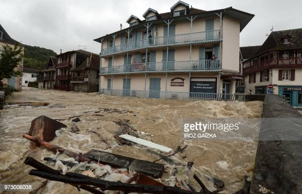 A person stands on the balcony of the top floor of a building watching as flood waters sweep through the streets following heavy rains in...