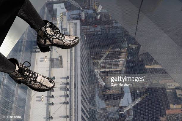A person stands on the glass floor of the Edge NYC an outdoor observation deck on the 100th floor of 30 Hudson Yards on its opening day on March 11...