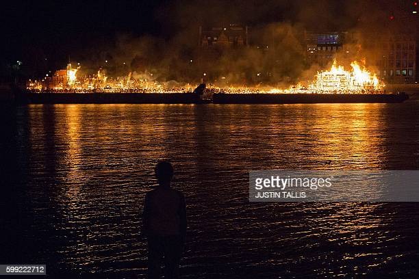 TOPSHOT A person stands on the shore watching a replica of 17thcentury London on a barge floating on the river Thames burning in an event to mark the...
