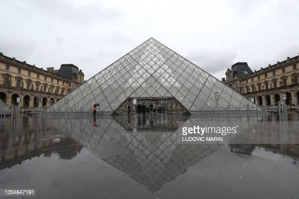 A person stands under an umbrella looking at the deserted courtyard outside the Louvre Pyramid the main entrance to the museum which was once a royal...