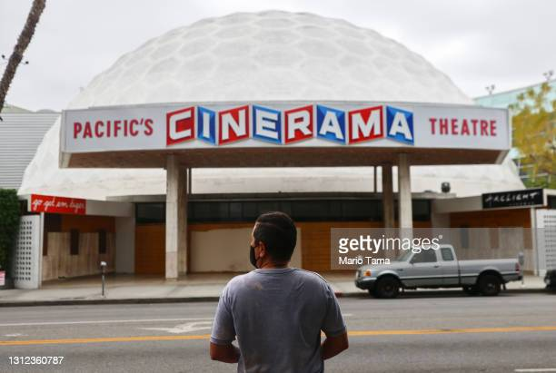 Person stands while taking photos of the famed Cinerama Dome at the shuttered ArcLight Hollywood movie theater on April 13, 2021 in Los Angeles,...