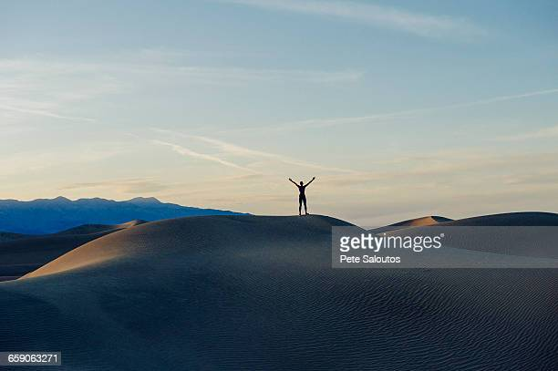 Person stretching arms at sunset, Death Valley, California, USA