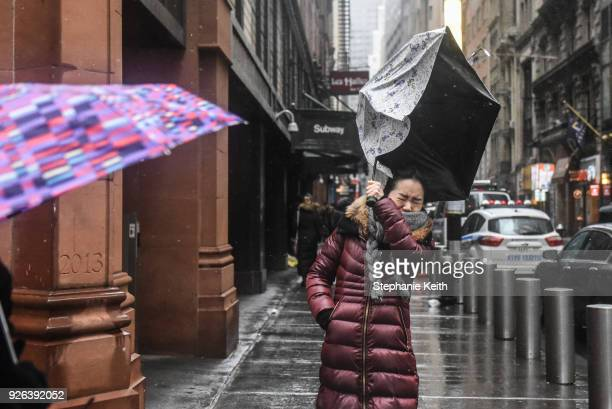 A person struggles with their umbrella during a large storm on March 2 2018 in New York New York A nor'easter is set to slam the East Coast on Friday...