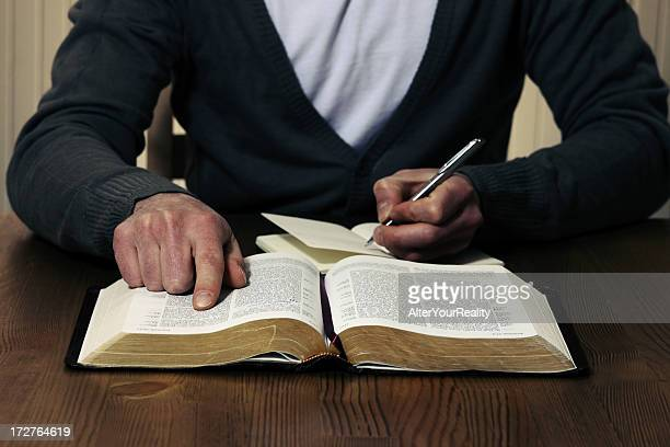Person studying the Bible with pen and notebook
