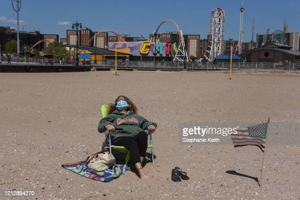 A person sunbathes while wearing a protective mask on May 13 2020 in the Coney Island neighborhood in the Brooklyn borough in New York City New York...