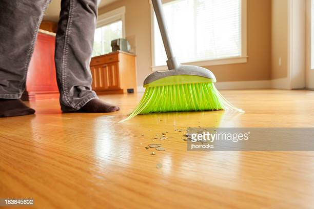 Person Sweeping Mess on Hardwood Floor with Broom