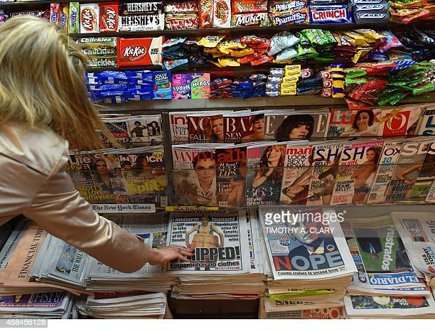 A person takes a copy of a New York Post at a newstand in Grand Central Station in New York November 5 2014 the morning after Republicans took the...