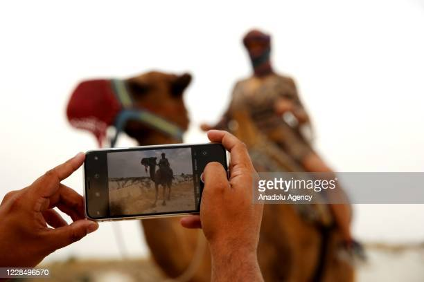 Person takes a photo of a tourist riding a camel while touring the fairy chimneys at the historical Cappadocia region, located in Central Anatolia's...