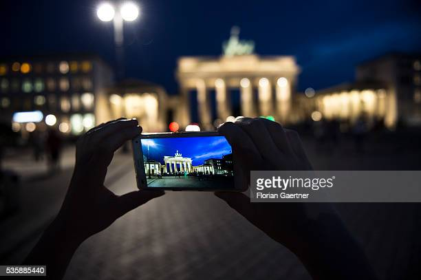 A person takes a photo of the Brandenburg Gate with his smartphone on May 29 2016 in Berlin Germany