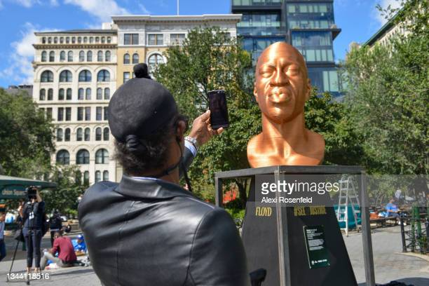 """Person takes a photo of the """"Floyd"""" sculpture after a press conference for Confront Art's First Exhibition launch SEEINJUSTICEin Union Square on..."""