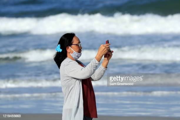 A person takes a photo on her mobile device on April 17 2020 in Jacksonville Beach Florida Jacksonville Mayor Lenny Curry announced Thursday that...