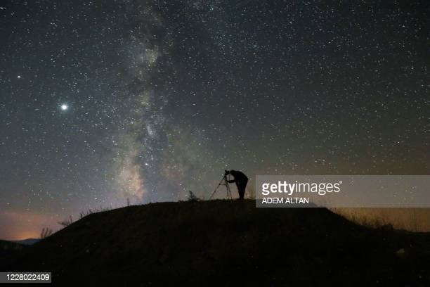 Person takes a photo with a camera on a tripod of the Milky Way at Nallihan district, in Ankara, on August 12, 2020.