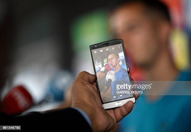 Person takes a photo with a smartphone as Real Madrid's Spanish midfielder Lucas Vazquez addresses journalists during Real Madrid's Media Open Day...