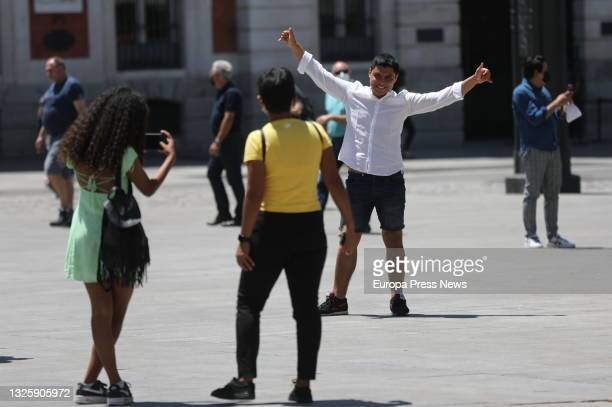 Person takes a photo without a mask in Sol, on June 28 in Madrid, . This is the first working day without the mandatory use of masks in open spaces...