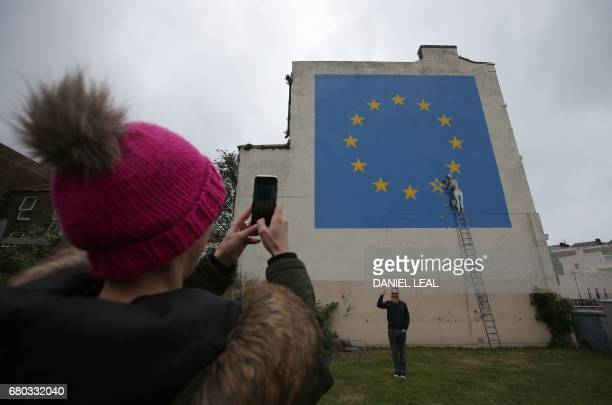 A person takes a photograph of a recently painted mural by British graffiti artist Banksy depicting a workman chipping away at one of the stars on a...