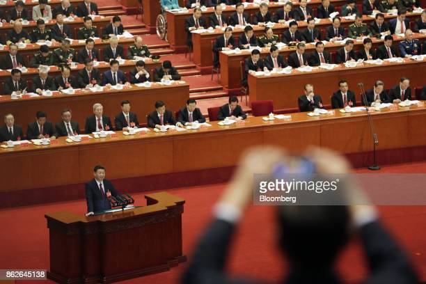 Person takes a photograph with a smartphone as Xi Jinping, China's president, speaks during the opening of the 19th National Congress of the...