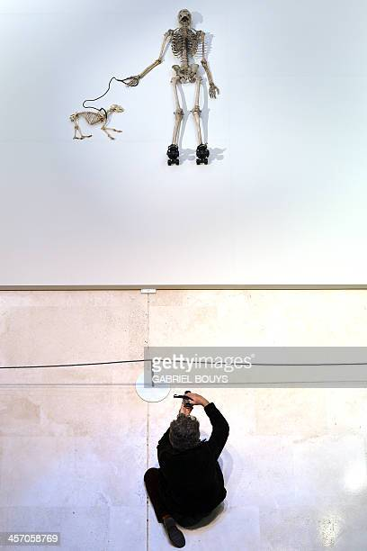 A person takes a picture of a piece of art by Gino de Dominicis called Time Error Space representing the skeleton of a man on rollerblades and his...