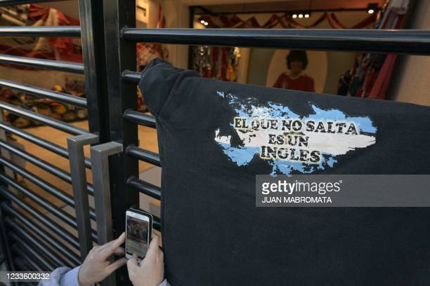 """Person takes a picture of a t-shirt with a map of the Falkland Islands reading """"The one that doesn't jump is an Englishman"""" outside the Diego Armando..."""