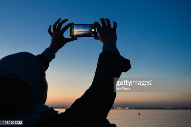 Person takes a picture of Dublin Bay at sunset with their mobile phone from Dun Laoghaire West Pier, during level 5 COVID-19 lockdown. On Saturday,...
