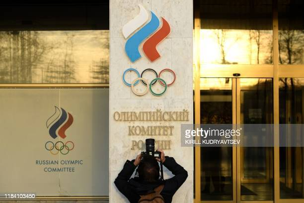 A person takes a picture of the Russian Olympic committee logo on the Russian Olympic committee headquarter in Moscow on November 23 2019 The...