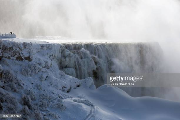 TOPSHOT A person takes a selfie beside on the US side of Niagara Falls as seen from Niagara Falls Ontario Canada on January 31 2019 A brutal cold...