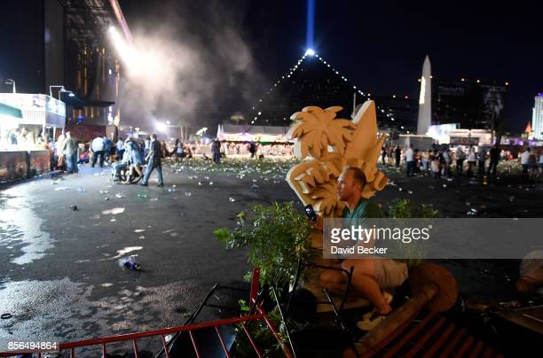 A person takes cover at the Route 91 Harvest country music festival after apparent gun fire was heard on October 1 2017 in Las Vegas Nevada There are...