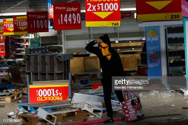 A person takes items from a looted supermarket during a protest against President Sebastian Piñera on October 23 2019 in Santiago Chile during the...