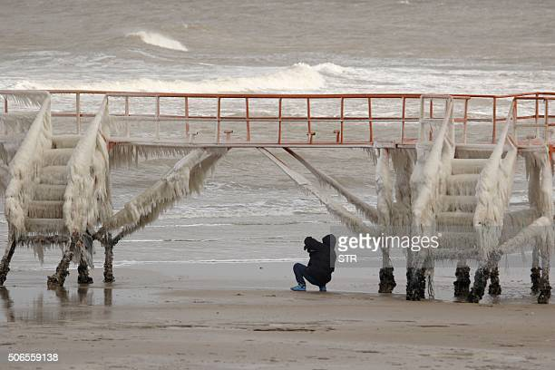 A person takes photos of icicles on a fence in Penglai in eastern China's Shandong province on January 24 2016 Much of China shivered on January 23...