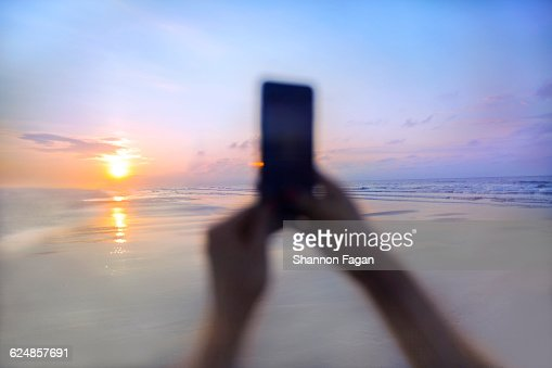 Person taking a photo at sunrise on the beach