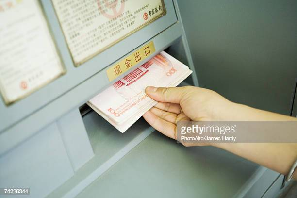 Person taking banknotes from ATM machine, cropped view